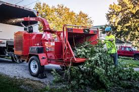 A man with a blue helmet, yellow shirt and blue pants putting tree limbs in a red chipper
